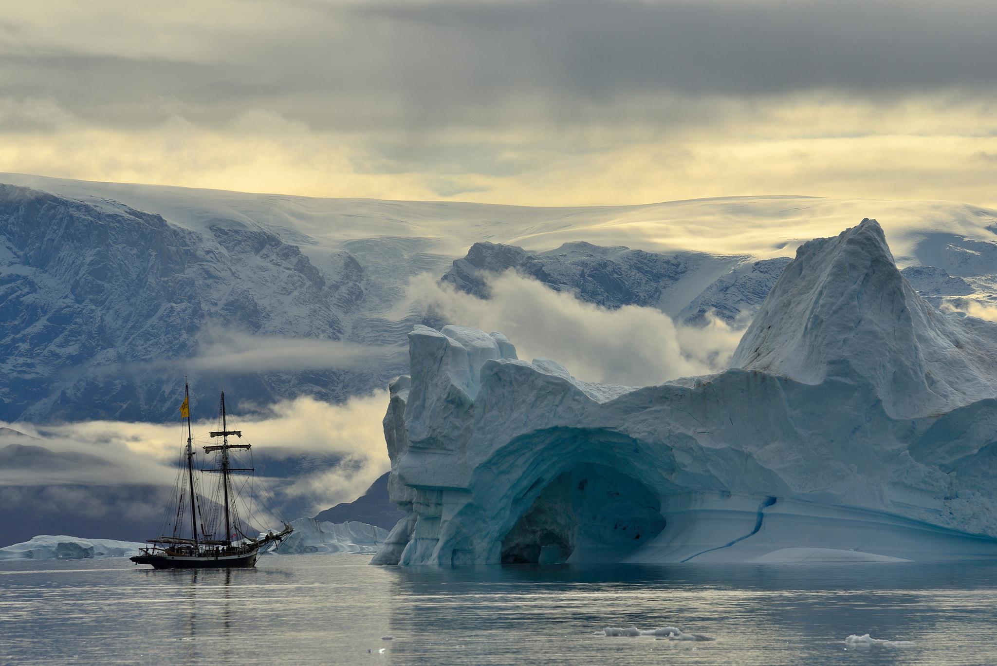 Een ijsberg en zeilschip in de fjord Kangertittivaq.